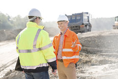 Happy engineer talking to colleague at construction site on sunny day Stock Photos