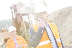 Happy engineer using walkie-talkie on construction site with colleague in background Stock Photography