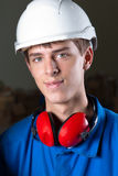 Happy engineer at work. Portrait of a happy engineer with safety helmet and earplugs Royalty Free Stock Photos