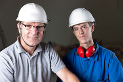 Happy engineers. Portrait of a happy senior and junior engineer with safety helmet, earplugs and glasses Stock Photo