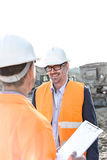 Happy engineers discussing at construction site against clear sky Stock Images