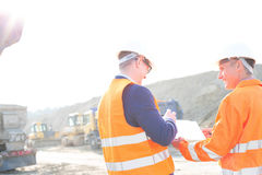 Happy engineers discussing over clipboard at construction site against clear sky Royalty Free Stock Photos
