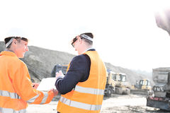 Happy engineers discussing over clipboard at construction site against clear sky Royalty Free Stock Image
