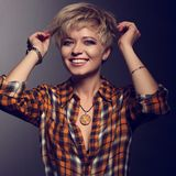 Happy enjoying blond young short hairstyle model laughing in bright yellow sell shirt holding the hair with orange necklace on da. Rk shadow grey background royalty free stock photos