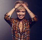 Happy enjoying blond young short hairstyle model laughing in bright yellow sell shirt holding the hair with orange necklace on da. Rk shadow grey background royalty free stock image