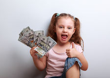 Happy enjoying kid girl holding money and showing thumb up sign Royalty Free Stock Image