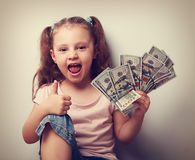 Happy enjoying kid girl holding money and showing thumb up sign. Stock Photo