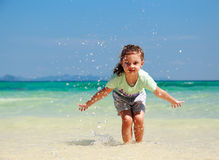 Happy enjoying kid girl playing and splashing with water on blue Stock Photo