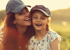 Happy enjoying mother hugging her laughing excited kid girl in b Royalty Free Stock Image