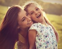 Happy enjoying mother hugging her laughing excited kid girl on s Stock Photo