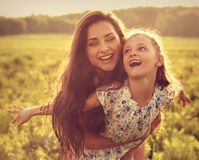 Happy enjoying mother hugging her playful laughing kid girl on s Stock Photos
