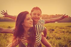 Happy enjoying mother hugging her playful laughing kid girl on sunset bright summer background. Closeup stock images