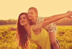 Happy enjoying mother hugging her playful laughing kid girl on sunset bright summer background. Closeup royalty free stock images