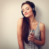 Happy enjoying woman listening the music in headphones with clos Royalty Free Stock Photos
