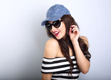 Happy enjoyment young woman in sun glasses and blue cap posing a Stock Photo