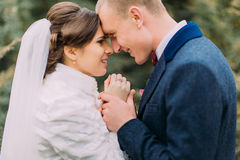 Happy enloved newlywed pair, tender bride and gentle groom, holding hands together while walking in green park Royalty Free Stock Photo