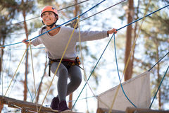 Happy enthusiastic woman having great time in the adventure park Royalty Free Stock Photo