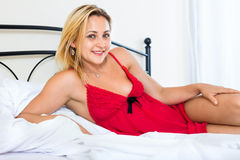 Happy enticing woman wearing underwear. On bed in bedroom stock images