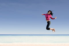 Happy entrepreneur jumping at beach Stock Images