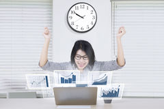 Happy entrepreneur with profit graph. Image of successful female entrepreneur celebrates her achievement while looking at virtual profit graph on the laptop in Stock Images