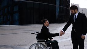 Happy entrepreneur shaking hands with disabled employee stock footage