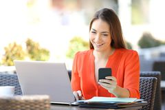 Happy entrepreneur using multiple devices in a coffee shop royalty free stock images