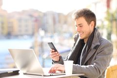 Happy entrepreneur using phone and laptop in a bar. Happy entrepreneur using smart phone and laptop in a bar terrace of a coast town stock image