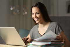 Entrepreneur working late hours looking at you. Happy entrepreneur working late hours in the night looking at you at home Royalty Free Stock Image