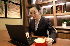 Young woman sitting in coffee shop at wooden table, drinking coffee and using smartphone.On table is laptop Royalty Free Stock Image