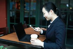 Young woman sitting in coffee shop at wooden table, drinking coffee and using smartphone.On table is laptop Stock Image