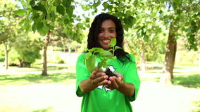 Happy environmental activist holding a shrub stock footage