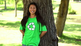 Happy environmental activist leaning against a tree stock video