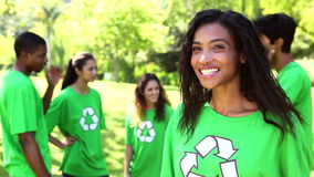 Happy environmental activist smiling at camera with team behind her stock footage