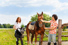 Happy equestrians preparing their horse for riding. Two happy equestrians, young women and men preparing their horse for riding at contryside Stock Photos