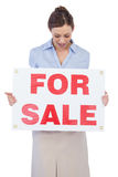 Happy estate agent posing with for sale sign. Against white background Stock Photos