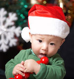 Happy etaing child. A baby wearing santa clothing and eating fruits at christmas eve Stock Photos