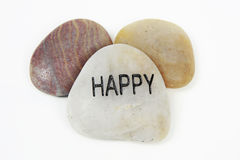 Happy etched in stone. Three different polished stones with happy etched in the front stone. Isolated against a white background royalty free stock photos