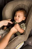 Happy ethnic Asian baby boy child put in carseat. Smiling biracial Asian Filipino kid sitting in car seat while parent hands buckle him up Stock Photography