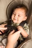 Happy ethnic Asian baby boy child put in carseat. Smiling biracial Asian Filipino kid sitting in car seat while parent hands buckle him up Stock Photos