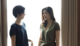Happy ethnic Asian friends smiling at window light royalty free stock photo