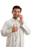Happy ethnic businessman on phone. Happy ethnic mixed race businessman on telephone with thumbs up approval, success hand sign.   He is wearing a traditional Royalty Free Stock Images
