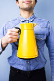 Happy ethnic man holding a jug Stock Photography