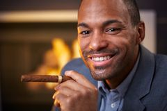 Happy ethnic man smoking cigar Royalty Free Stock Images