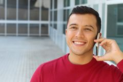 Happy ethnically ambiguous male calling by phone.  royalty free stock photos