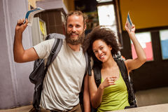 Happy and euphoric couple of backpacker tourists show tickets fo. Very happy and euphoric couple of backpacker tourists show purchased tickets for their long Royalty Free Stock Photos