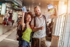 Happy and euphoric couple of backpacker tourists show tickets fo. Very happy and euphoric couple of backpacker tourists show purchased tickets for their long Royalty Free Stock Image