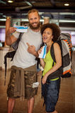 Happy and euphoric couple of backpacker tourists show tickets fo. Very happy and euphoric couple of backpacker tourists show purchased tickets for their long Royalty Free Stock Images