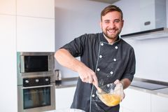 A happy man is cooking whipping egg yolks with a kitchen whisk. The concept of cooking. A happy European brunette man is cooking in the kitchen, whipping egg Royalty Free Stock Photography