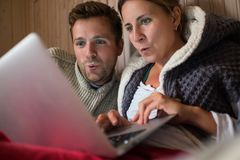 Happy european family making shopping in internet using laptop. stock photo