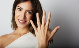 Happy european girl with long dark hair in stylish clothes smiling and holding hand on hip while showing trendy wedding. Ring over empty gray wall background stock images